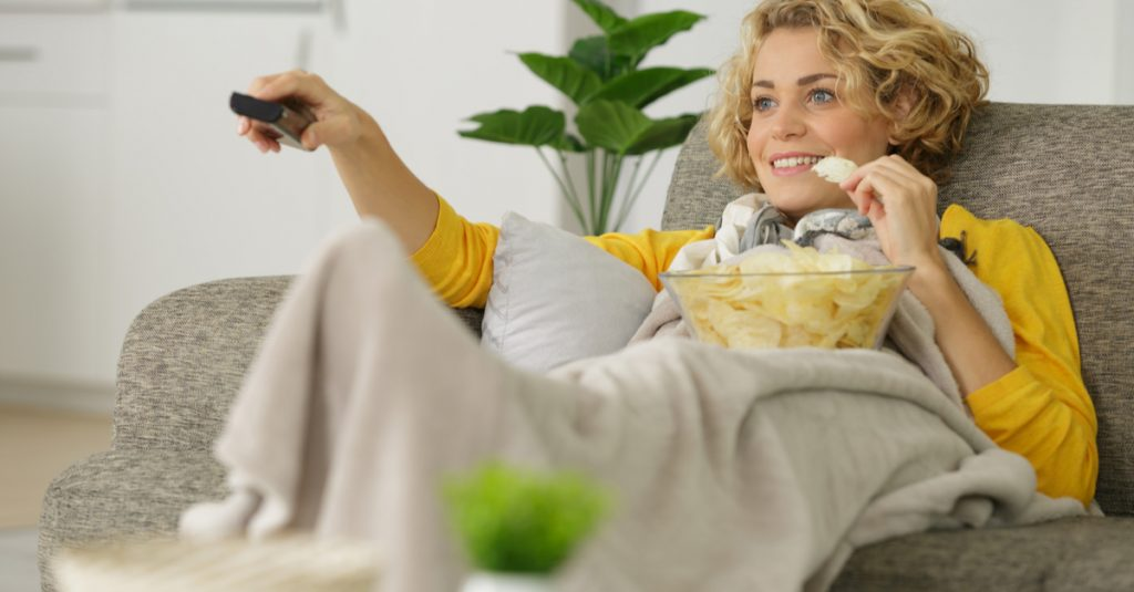 A woman relaxes and enjoys life from the comfort of her own couch.