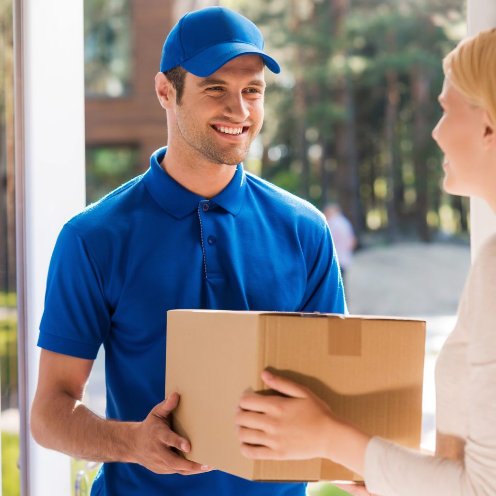 A delivery person drops off a package to a happy customer.