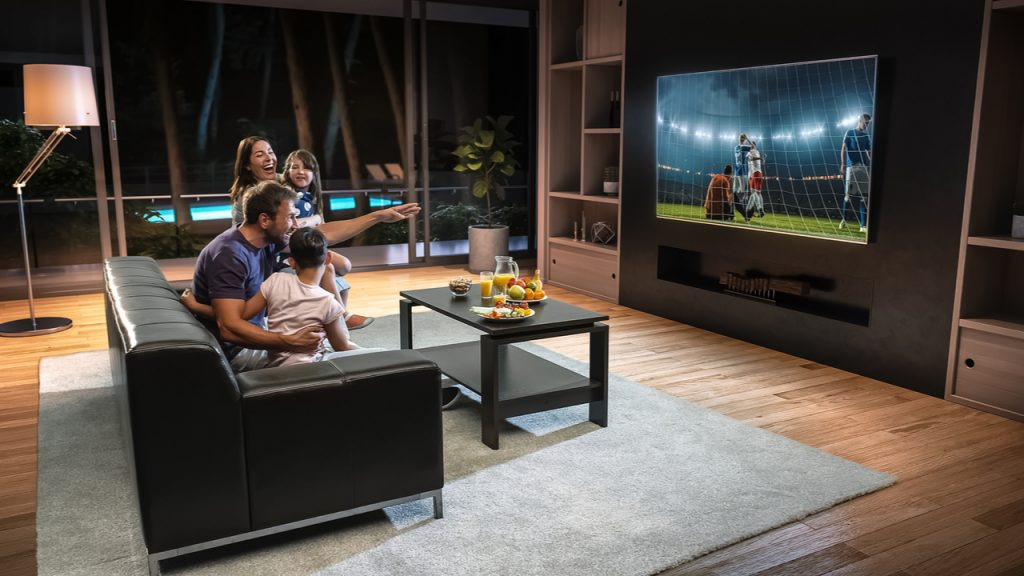 A family watches an exciting soccer game on TV together.