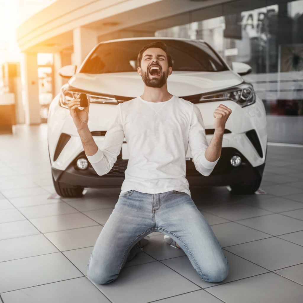 A man is overcome with joy as he is handed the keys to his new car.