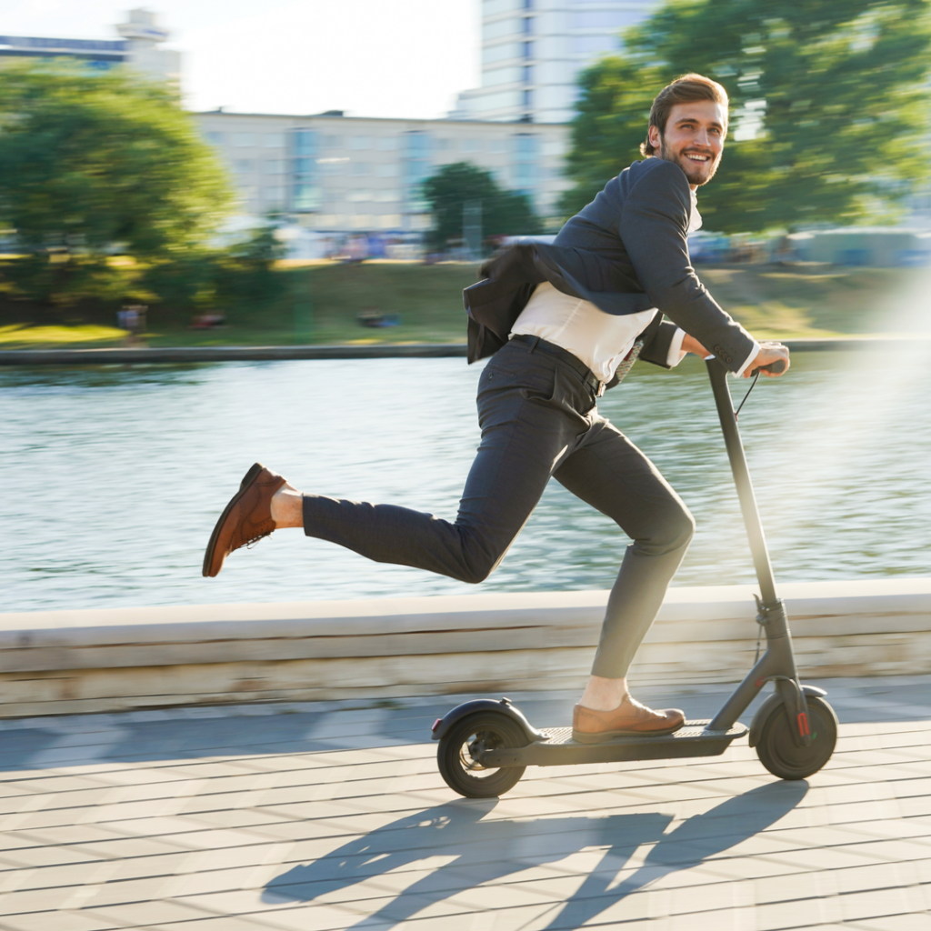 A young businessman happily commutes to work on an electric scooter-an item DealDash has up for auction.