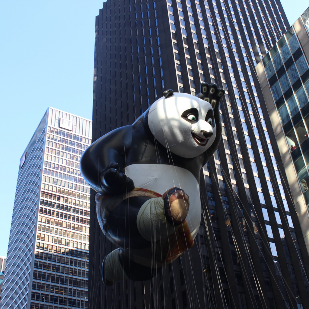 A large balloon panda floats over the crowd at a holiday parade in New York City.