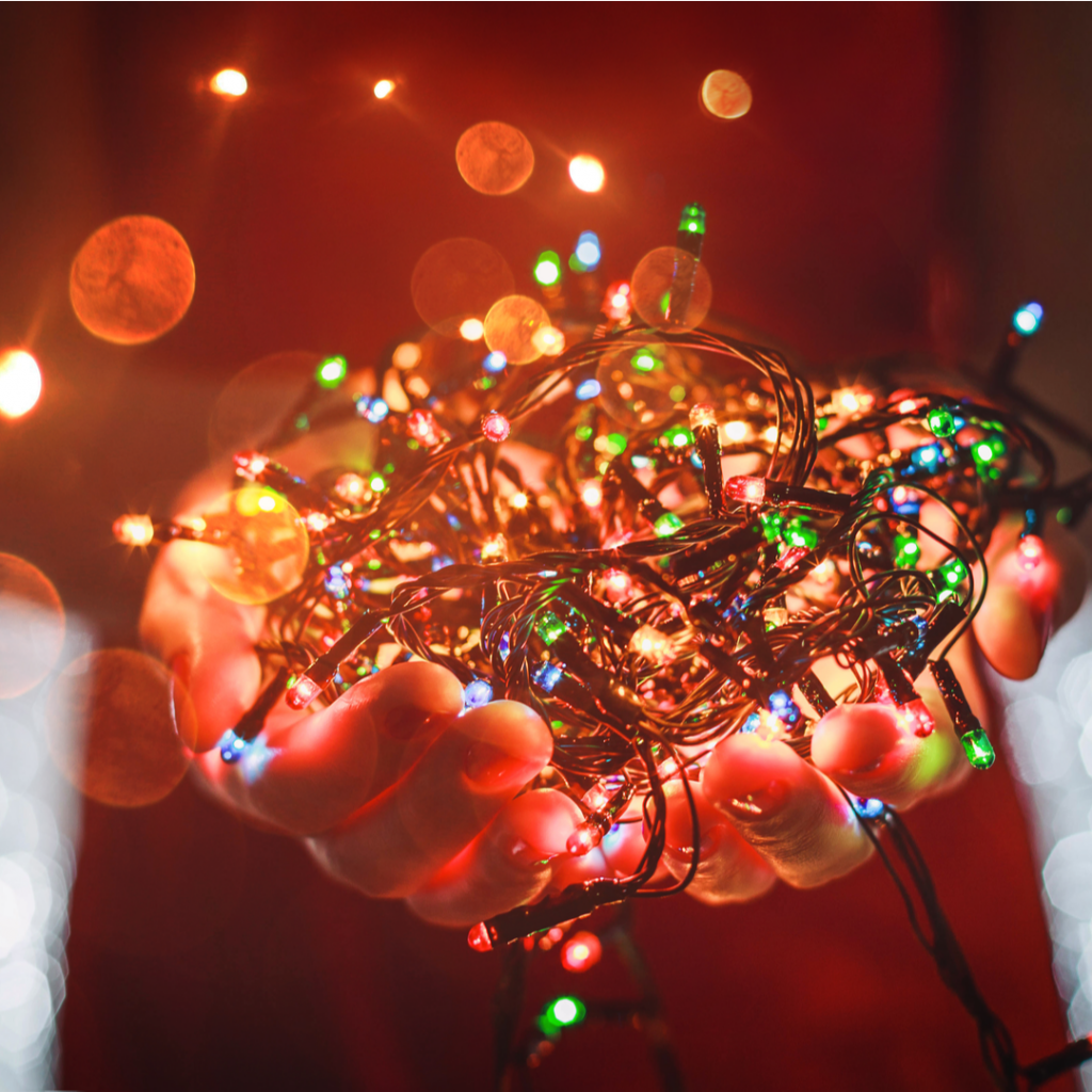 A person holds a handful of Christmas lights as they prepare to begin decorating.
