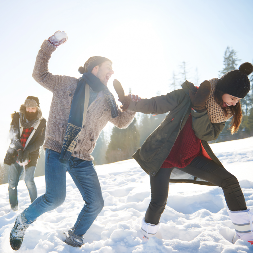 A group of friends enjoy a fun snowball fight together on a beautiful winter day.