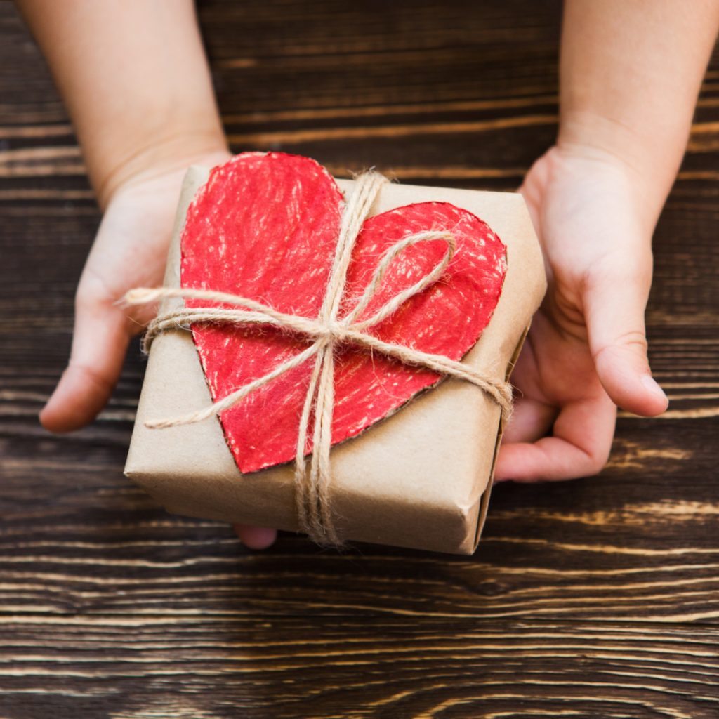 A pair of hands holds a wrapped Christmas gift in a display of generosity.