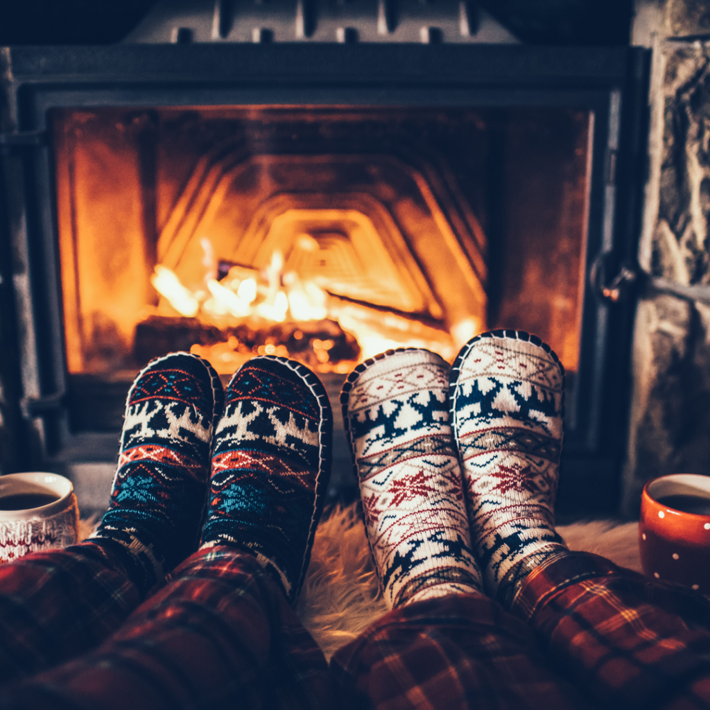 Two pairs of feet warm themselves in front of a fireplace.