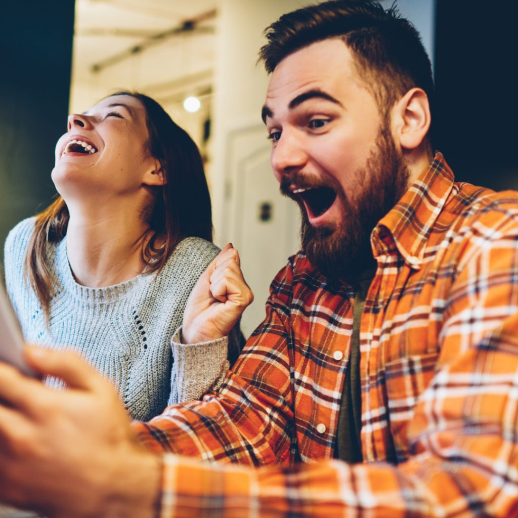 A man and a woman shout with excitement as they use the DealDash App on their phones.