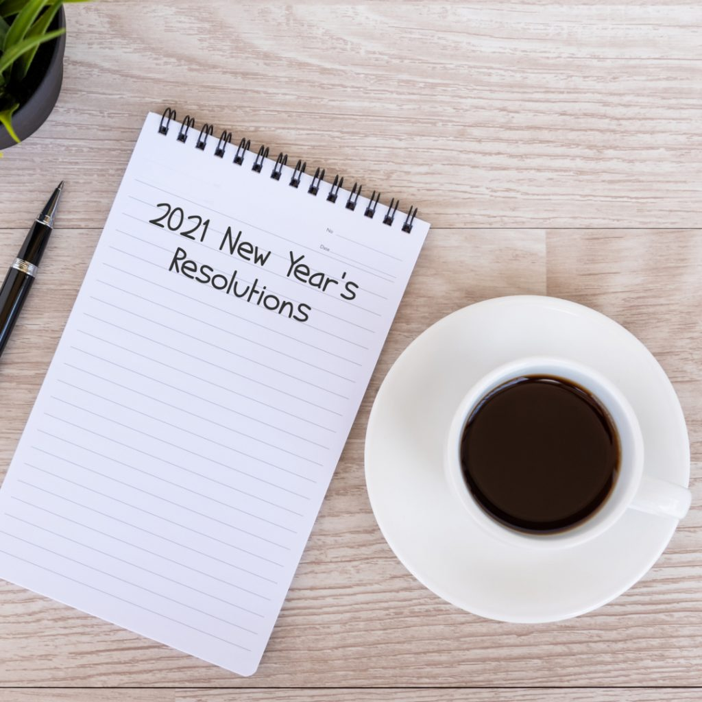 A note pad and a pen wait on a table next to a cup of coffee.  The pad is to be filled out with New Year's resolutions for 2021.
