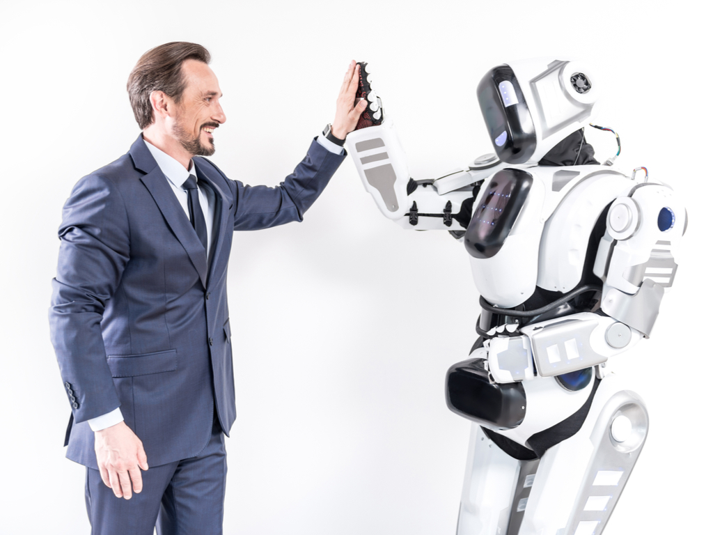A man gives a friendly greeting to aa robot which represents the BidBuddy tool DealDash provides.