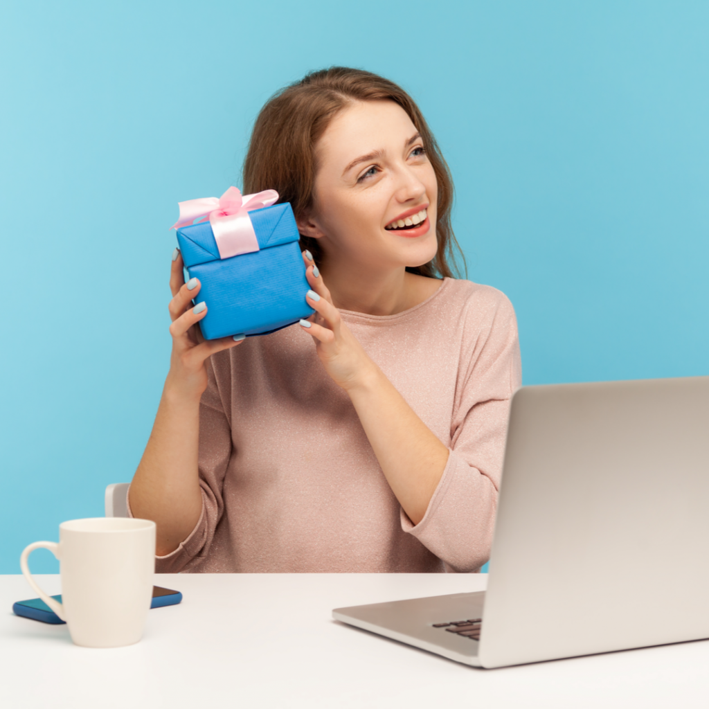 A woman holds up a small wrapped gift while sitting in front of her computer.