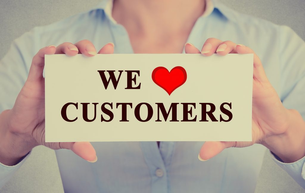 A person holds up a small sign that reads, 'we love our customers.'