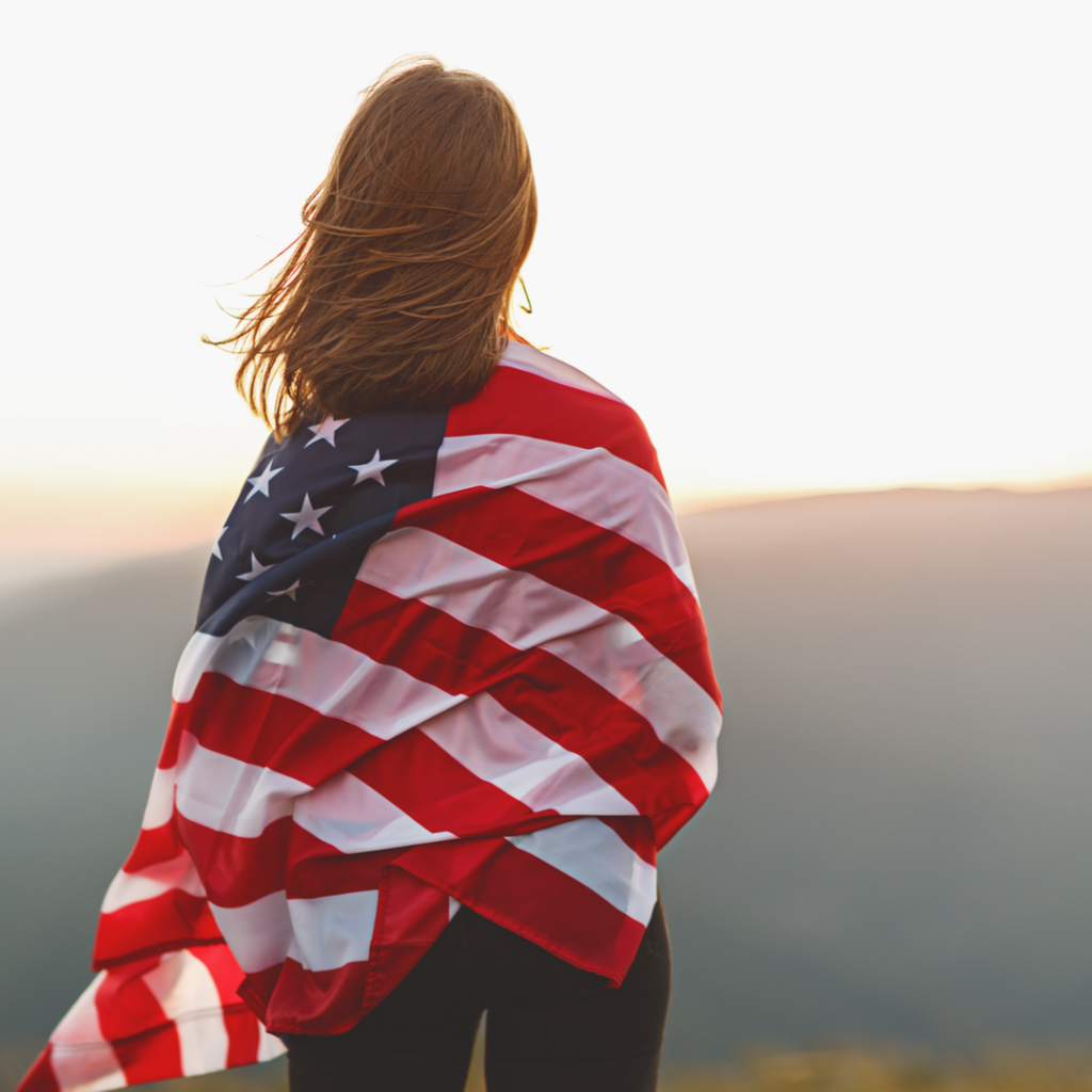 A young woman is wrapped in the American flag and gazes over the countryside.