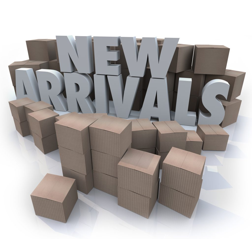 A stack of boxes stand behind large text that says, 'New Arrivals'.