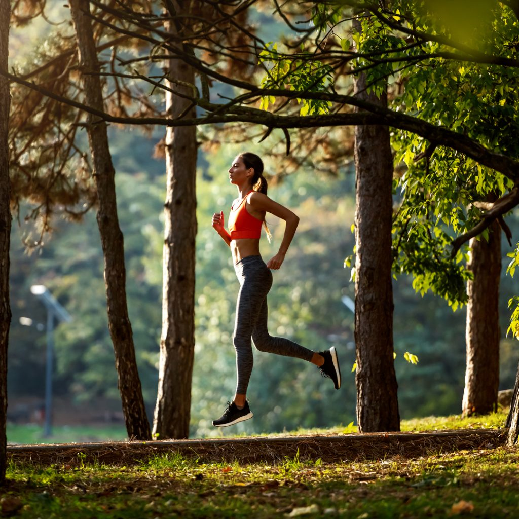 A woman enjoys a nice jog through a sunny forrest.