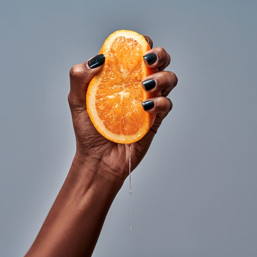 A hand squeezes an orange to make orange juice.