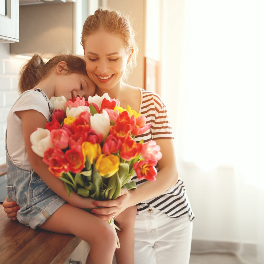 A mother and daughter embrace while enjoying a bouquet of tulips on Mother's Day.