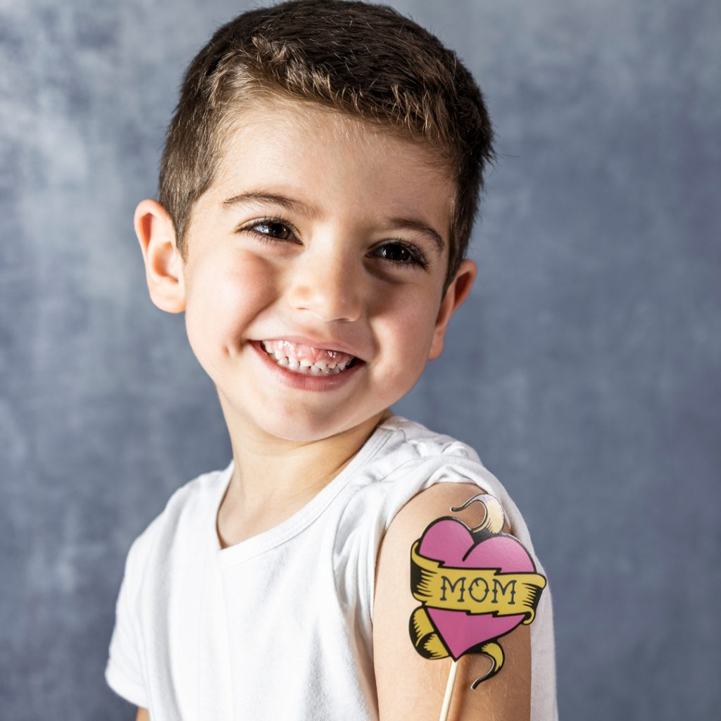 A young boy smiles for the camera with a fake tattoo on his arm that says 'Mom'.