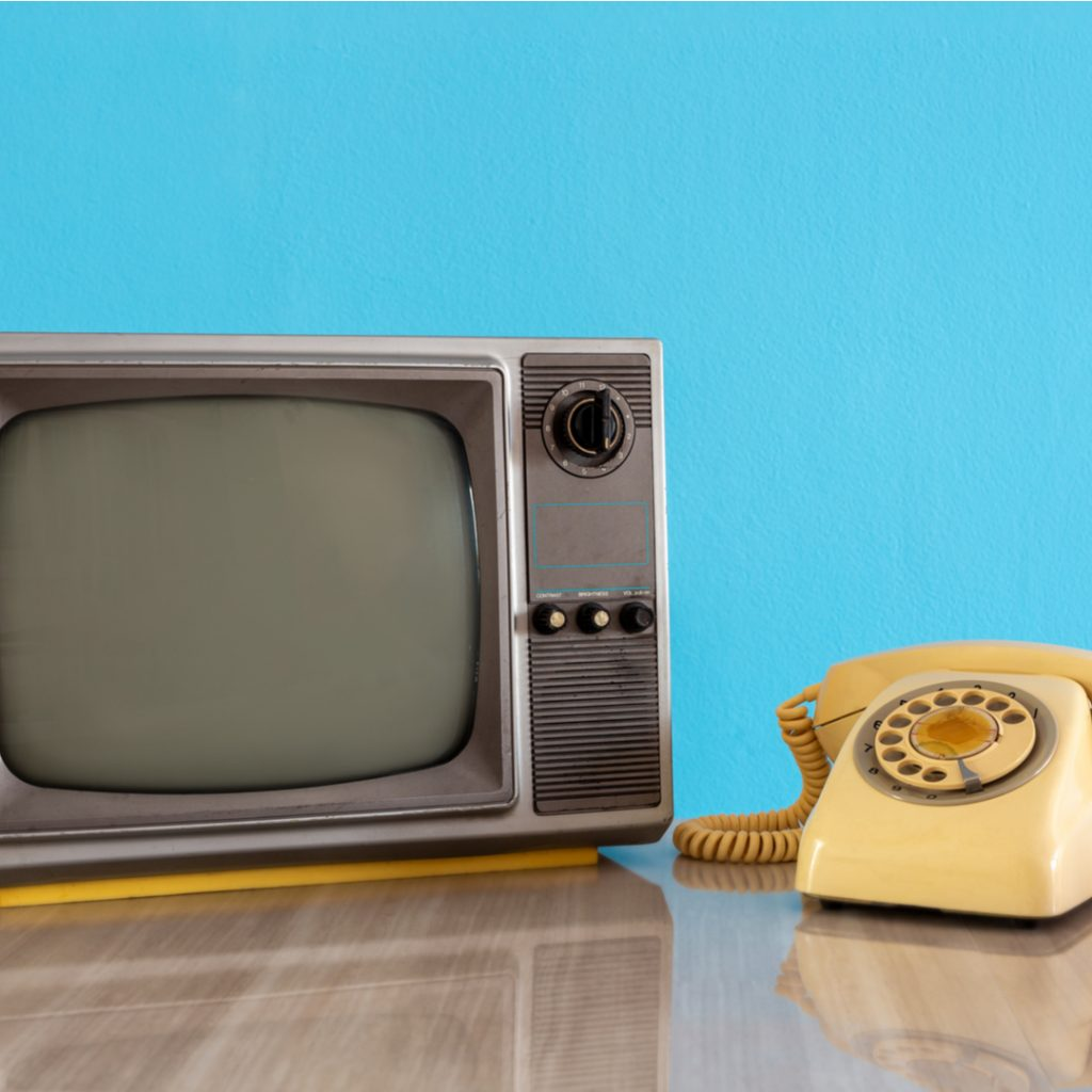 A vintage TV and telephone sit on a wooden table.
