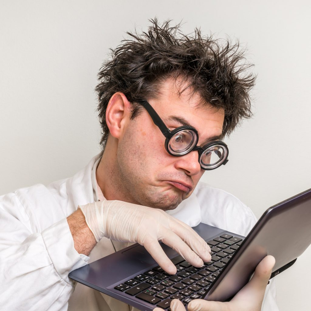 A disheveled scientist holds up a laptop as he frantically works on his latest creation.