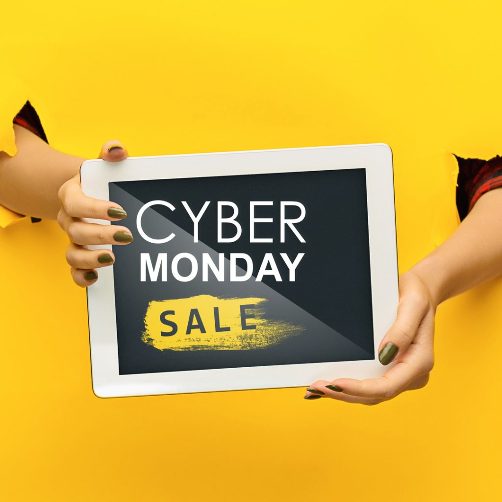 Hands holding a tablet announce a Cyber Monday sale.