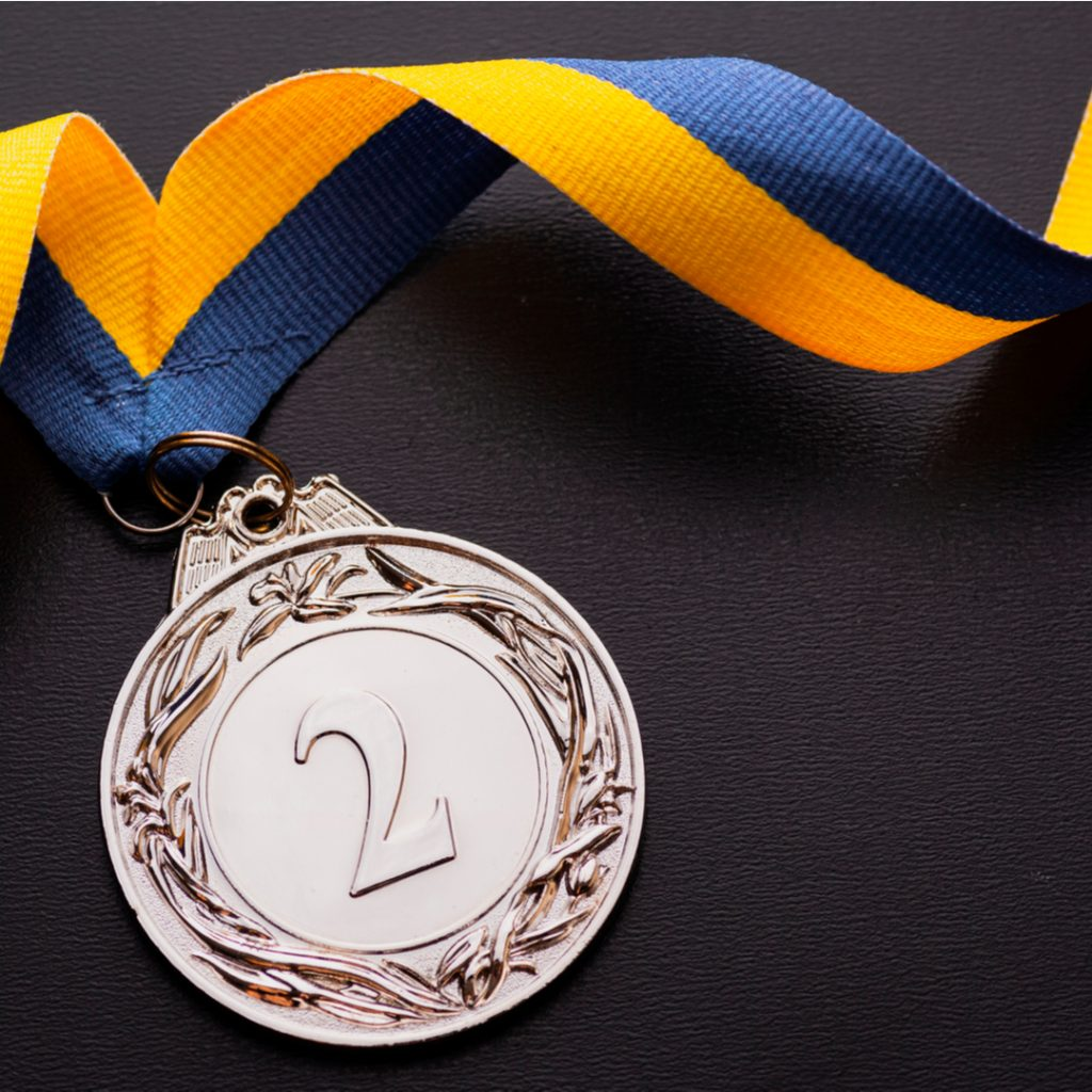 A silver medal attached to a colorful ribbon lies on a table and is  a handsome reward for finishing second.