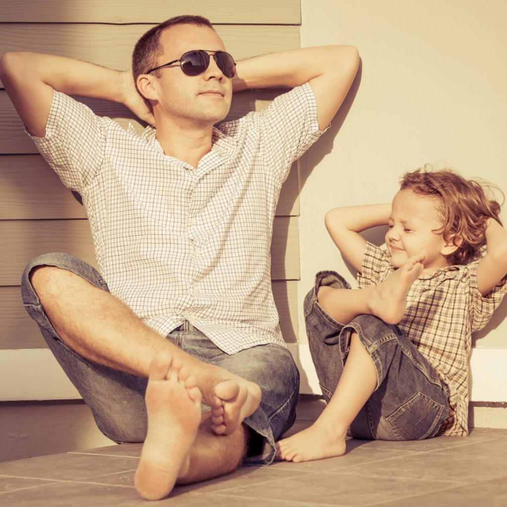 A father and son both relax and enjoy a moment in the sunshine.