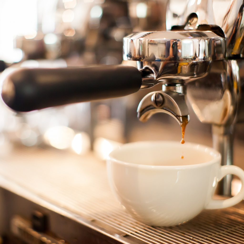 A cup of specialty coffee is being made on a deluxe coffee machine.