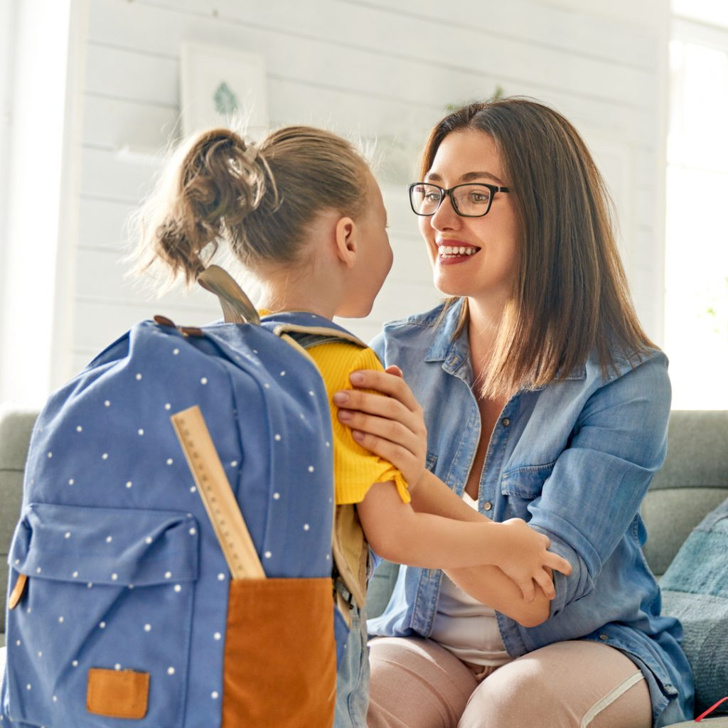 A mother gives a pep talk to her daughter to prepare her for the first day of school.