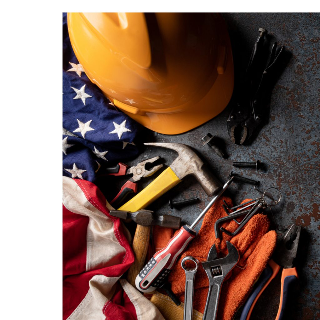 Tools and a construction helmet lie next to an American flag.