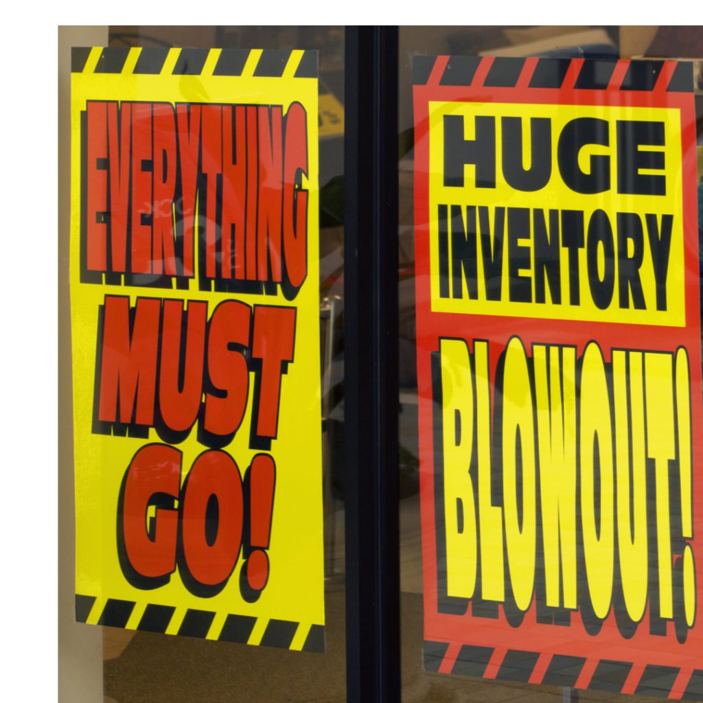 Signs in a store window advertise a sales event where everything must go.